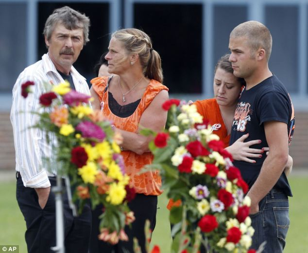 Pained: Somber friends gather outside the high school following the service before heading to the burial