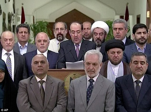 Iraq's prime minister  for the past eight years, Nouri al-Maliki (centre), speaks at a podium surrounded by Iraqi MPs yesterday. Al-Maliki stepped down in favour of fellow Dawa Party member Haider al-Abadi (stood to al-Maliki's right)