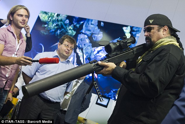 Big guns: Action star Steven Seagal was pictured at an arms fair in Russia yesterday, trying his hand with the equipment