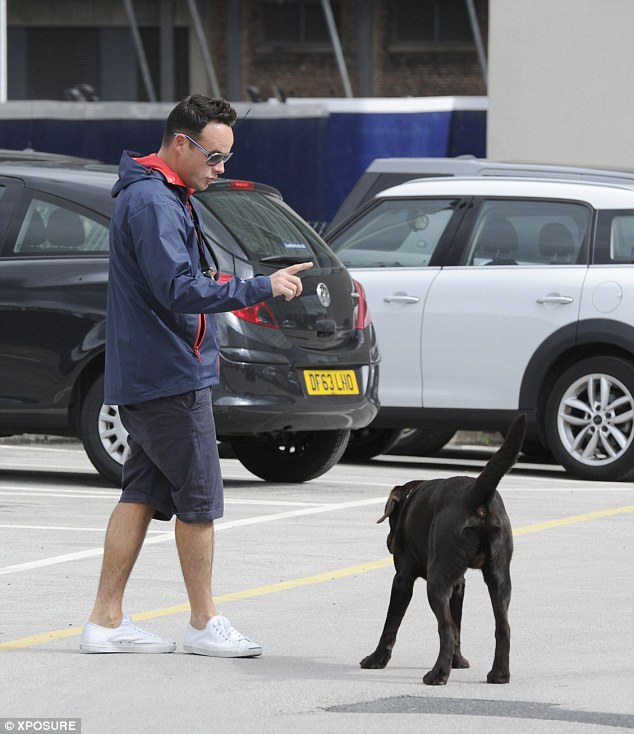 Keeping his cool: Ant cut a cool figure in his knee-length shorts and matching raincoat, which he teamed with white trainers