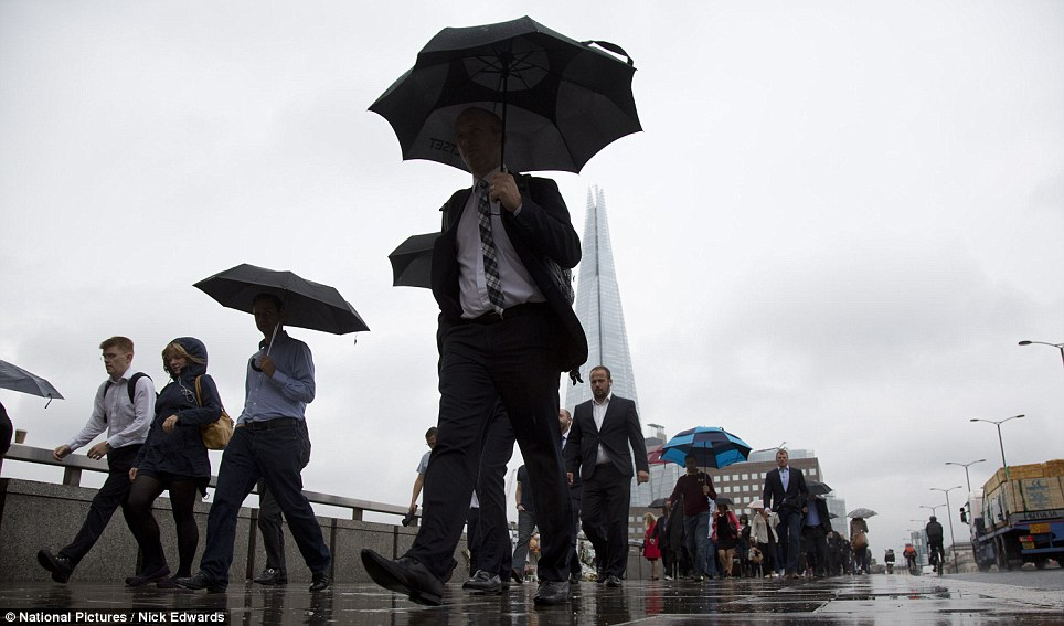 Early start: Heavy rain forced commuters walking across London Bridge in the centre of the capital to put up their umbrellas as they headed to work