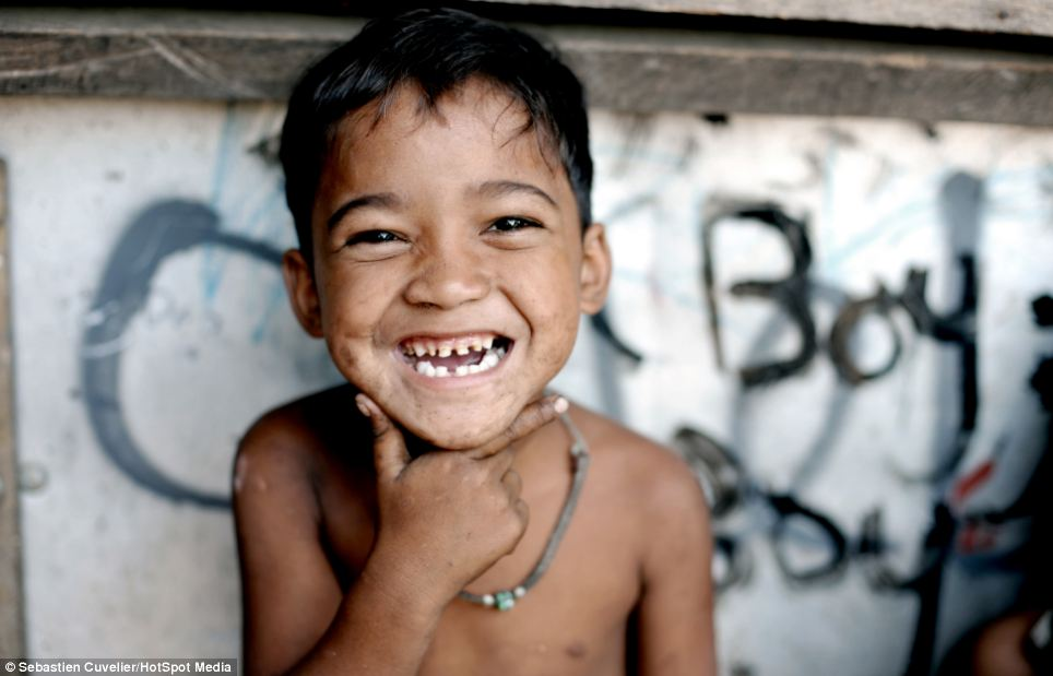 A little boy smiles for the camera after being pictured by Belgian photographer Sebastien Cuvelier, while sitting next to a dumping site in Payatas, Manila