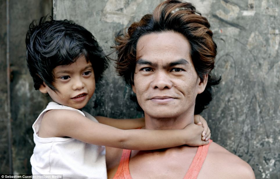 A man and his son pose outside their makeshift house in Divisoria, Manila, one of four slums that Mr Cuvelier visited on his two month trip to the Philippines