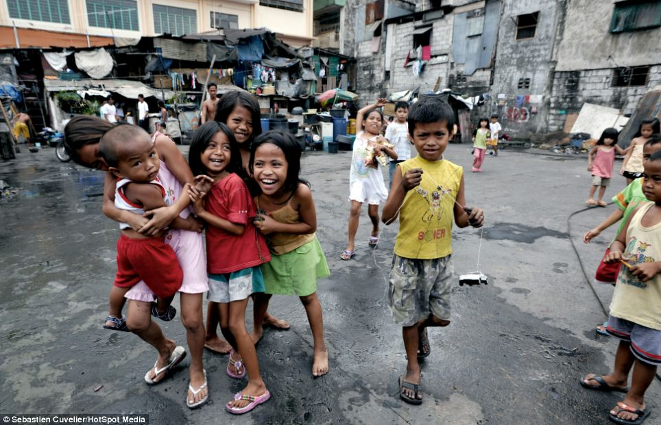 Despite being surrounded by squalor in the makeshift shanty town of Tondo in Manila, these children can't help but smile as they play in the street
