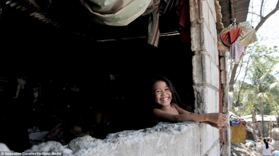 A young girl smiles at passers-by who walk past her makeshift house built next to a dump in Payatas