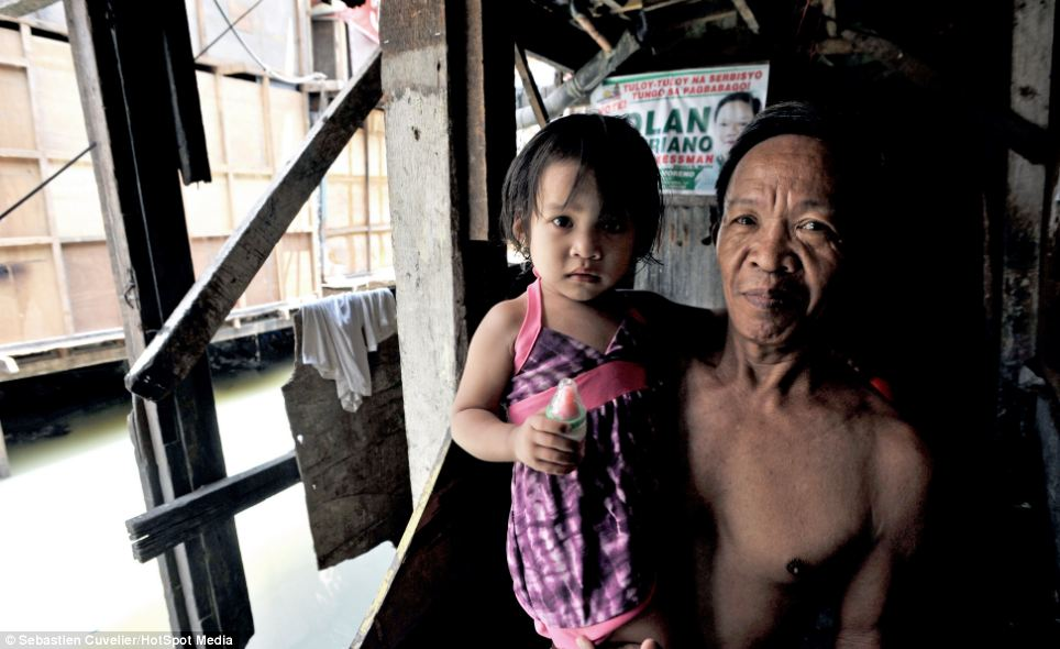 A man proudly carries his grand-daughter outside of his shack built over a canal near Divisoria while being pictured by Mr Cuvelier
