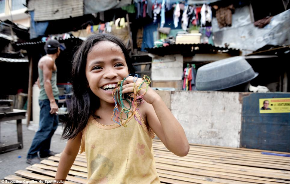 A young girl collects rubber bands and ties them together to make a bracelet and necklace, resembling the recent loom band craze