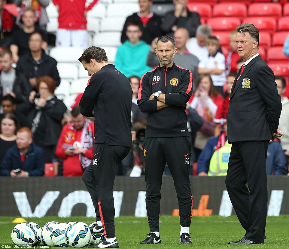 Pre-match nerves: Van Gaal and   Giggs look on as United warmed up before their first Premier League match of the new season