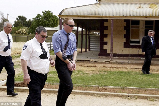 Robert Wagner, pictured in 2002, being escorted by a court sheriff outside the house in Snowtown, where for a time Wagner stored the bodies in barrels in the driveway in the back of a car. The photograph was taken when the jury in the bodies-in-the-barrels trial visited the small town for the trial.