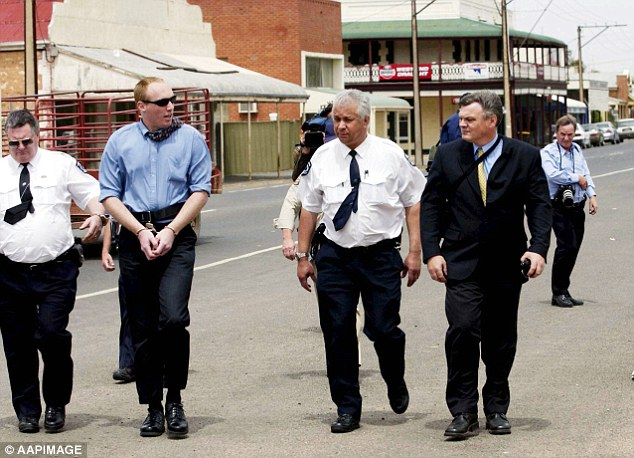 Robert Wagner, pictured second from left in handcuffs, being escorted by police through the town of Snowtown during his trial for murder in 2002. In the background is a brick building, in which eight bodies were discovered in 1999.