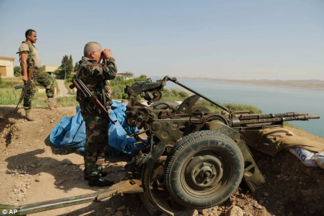 Kurdish troops stand guard in Chamibarakat, close to the dam, which was taken by Jihadi forces two weeks ago