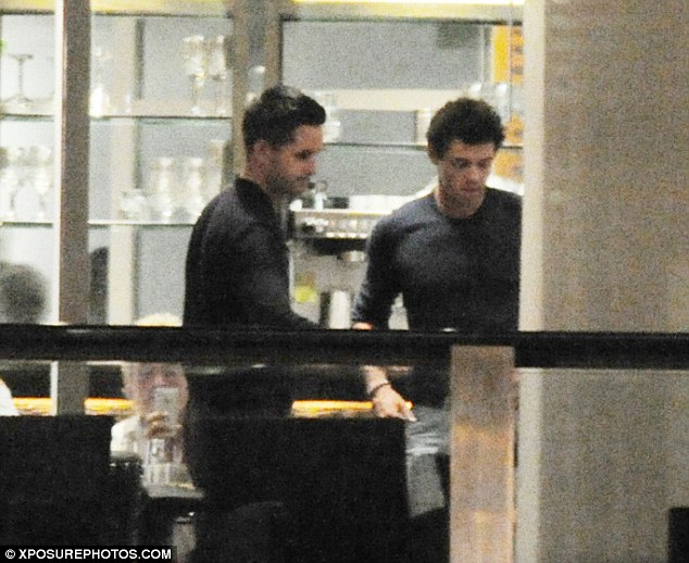 Catching up: Rory and his pal had a little chat as they chilled out in the hotel bar