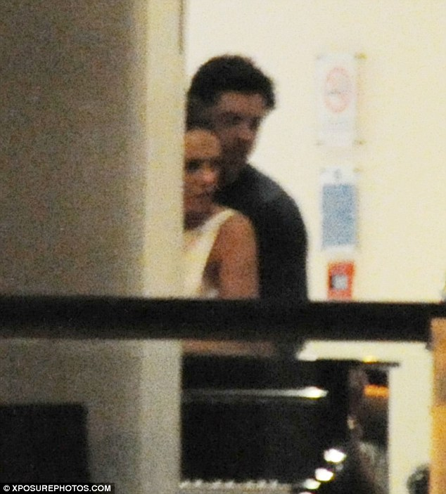Cuddle time: The sportsman placed his arms around a brunette who wore a white bodycon dress
