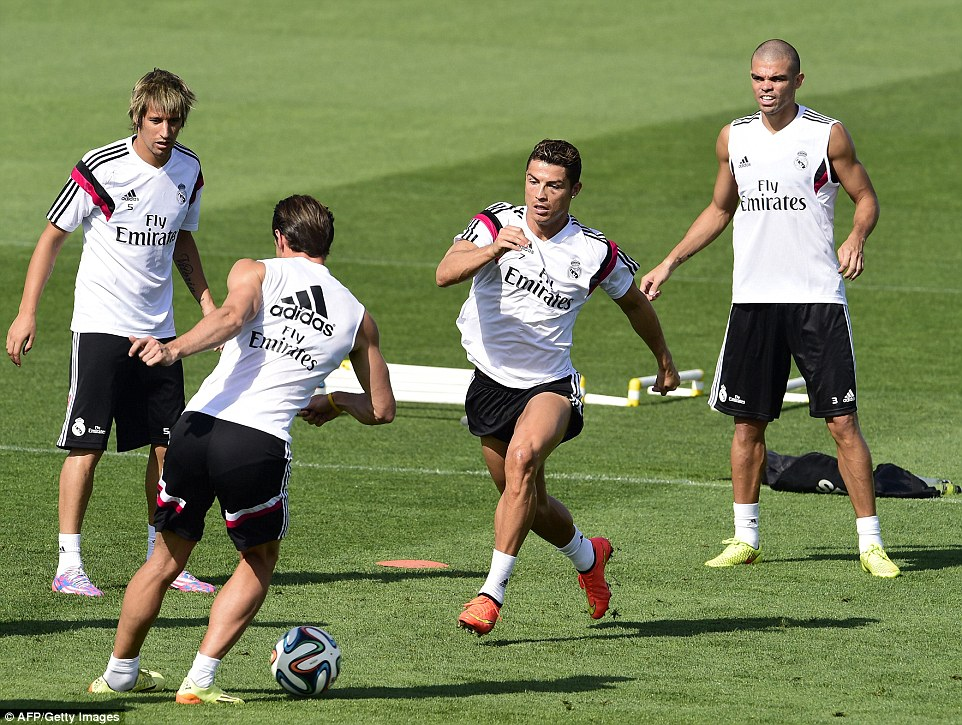 Challenge: Cristiano Ronaldo charges in to tackle Gareth Bale whilst defenders Fabio Coentrao and Pepe watch on
