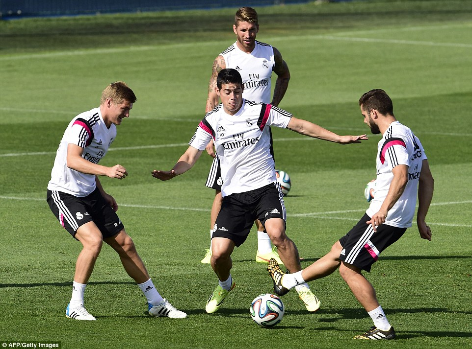 Piggy in the middle: Rodriguez tries to win the ball off Dani Carvajal and Kroos whilst Sergio Ramos watches on