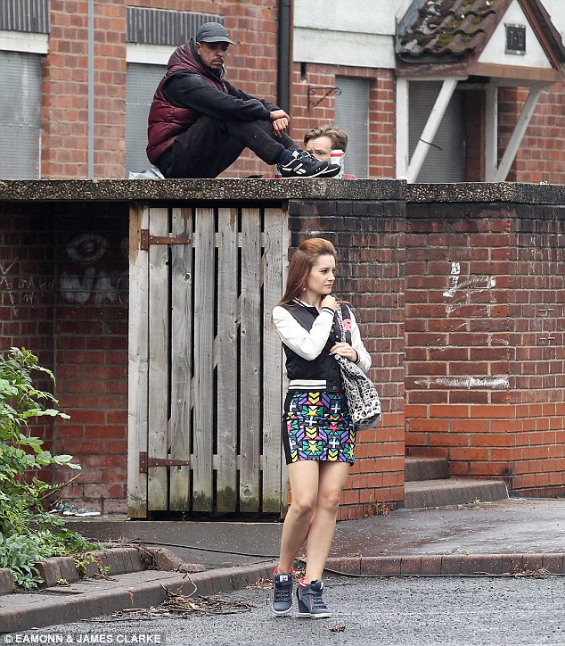 Standout: Dressed in a colourful patterned mini dress, the look was completed with a black and white baseball jacket and a pair of navy wedged trainers