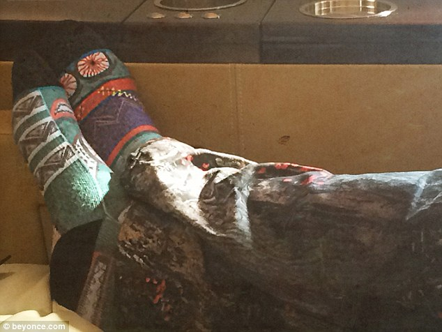 Colourful: Jay Z sports green-patterned socks and stonewashed jeans as he lies with his legs crossed