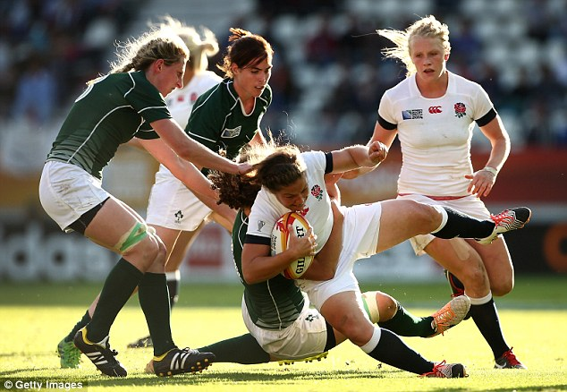 Mrs Croker, from Essex, is pictured being tackled in the World Cup semi-final against Ireland. The England team took the title for the first time in 20 years
