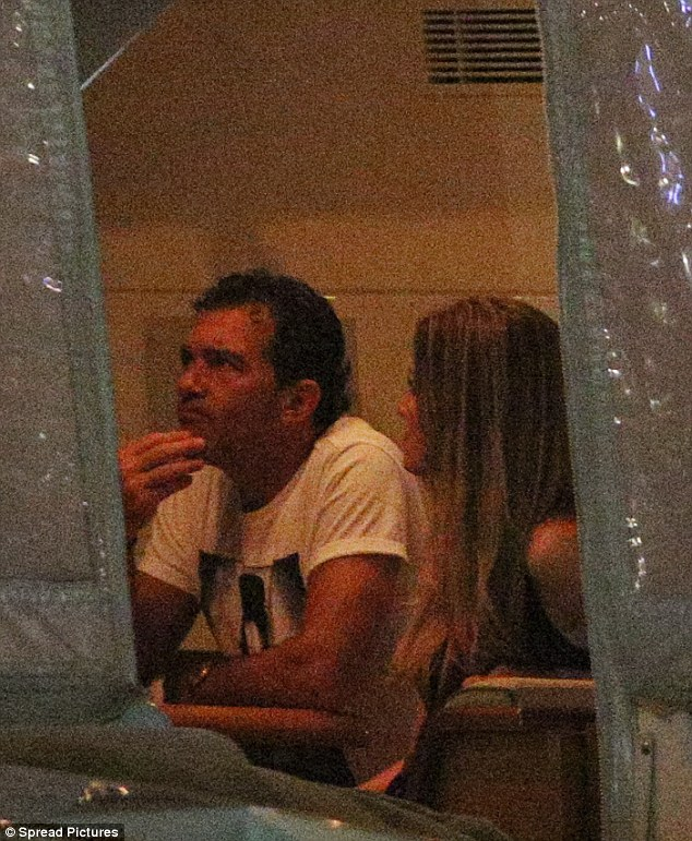 Cosy: Once safely inside their sea-going vessel, Antonio removed his blue blazer and sat right beside his new ladylove