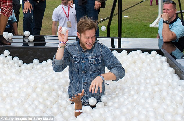 Child's play: Olly Murs was spotted larking around in the Xperia Access ball pit as he enjoyed himself at the festival on Sunday
