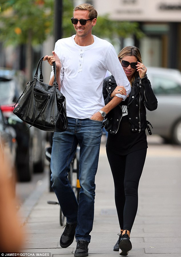 He's a gent! Peter Crouch carries wife Abbey Clancy's handbag during a leisurely stroll in London on Tuesday