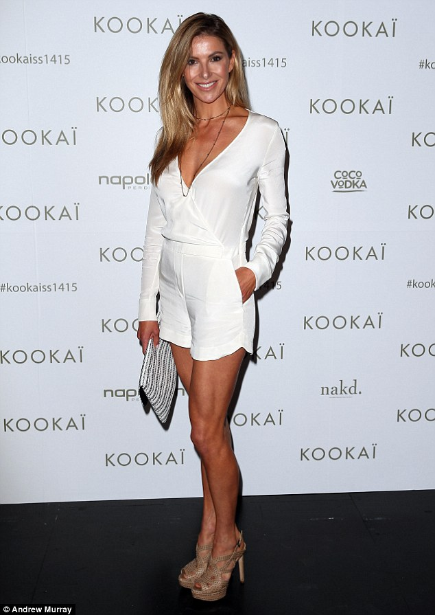 Delight in white! She teamed her jumpsuit with a matching purse and a beig pair of studded heels