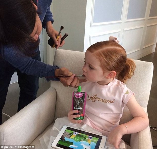 In the makeup chair: Three-year-old Pixie Curtis - the daughter of Sydney PR queen Roxy Jacenko - pretends to get her makeup done by Sydney professional Norman Gonzales on Wednesday