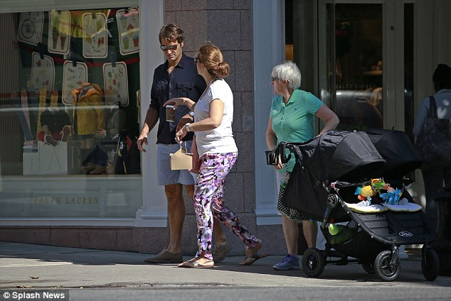 Keeping hydrated: Mirka was seen handing her husband a hot beverage as the waited to cross