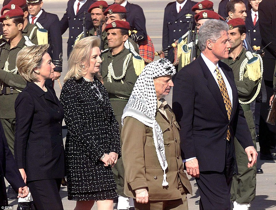 US President Bill Clinton (right) and his Palestinian counterpart Yasser Arafat, accompanied by their wives, Hillary Clinton (left) and Suhah Arafat, review Palestinian honour guards before the opening of the airport