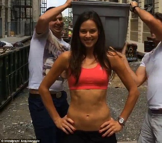 Dunked: Ana Ivanovic has ice poured over her by two guys after taking part in the Ice Bucket Challenge