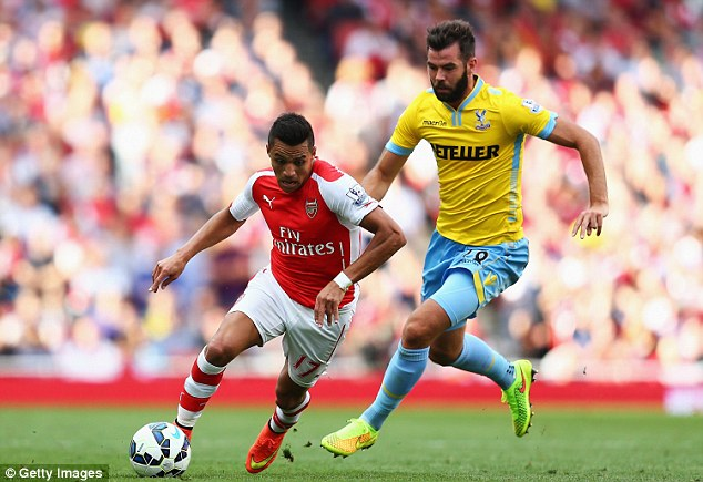 Little and large: Alexis Sanchez turns away with the ball as Palace's Joe Ledley tries to catch up with him