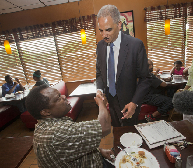Bridges: Attorney General Eric Holder stops to shake hands with a patron at Drake's Place Restaurant, before his meeting with local community leaders on Wednesday