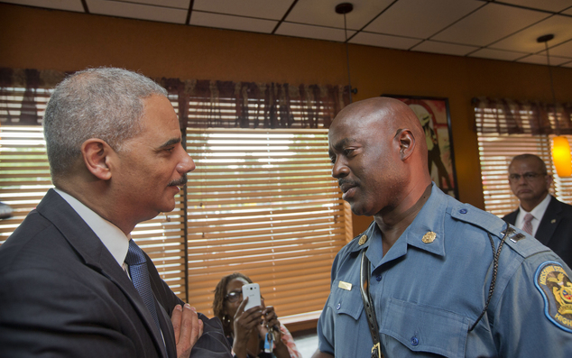 Meeting: Attorney General Eric Holder speaks with Capt. Ron Johnson of the Missouri State Highway Patrol at Drake's Place Restaurant, on Wednesday