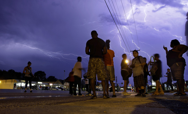 Anger: Protesters stand in the street as lightning flashes in the night sky in Ferguson, Missouri on Wednesday night