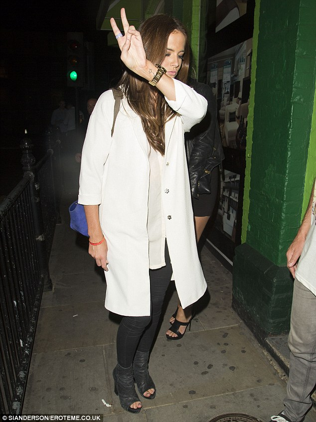 Give peace a chance: Binky flashes the two fingered sign as she makes her way inside