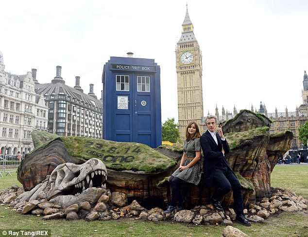 London calling: Doctor Who and his assistant pose on a large rock in front of Parliament Square, with a large dinosaur head