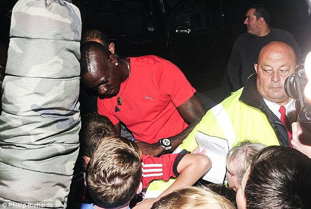 In demand: Balotelli signed autographs for young supporters as he left Melwood later on Friday