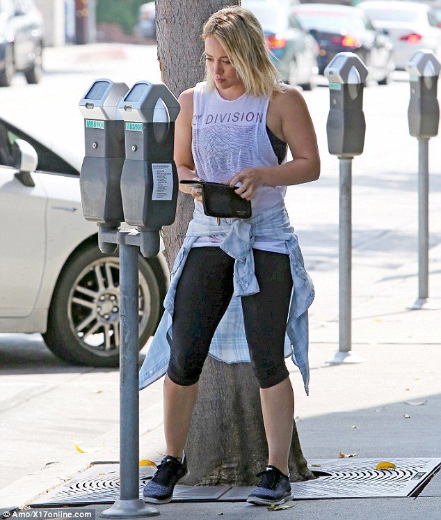 Just like us: Hilary was seen feeding her meter as she stood in her athletic wear