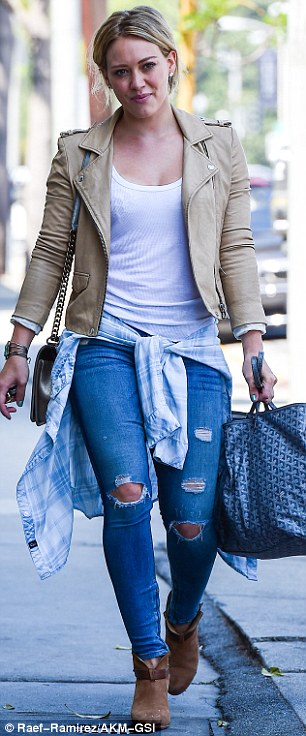 Stylish: The mother-of-one looked chic n a white shirt, tan biker jacket, tattered skinny jeans and tan suede booties
