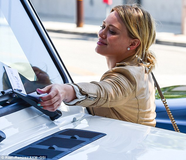 Graceful girl: The blonde was seen grabbing the ticket from the windshield of her Mercedes SUV