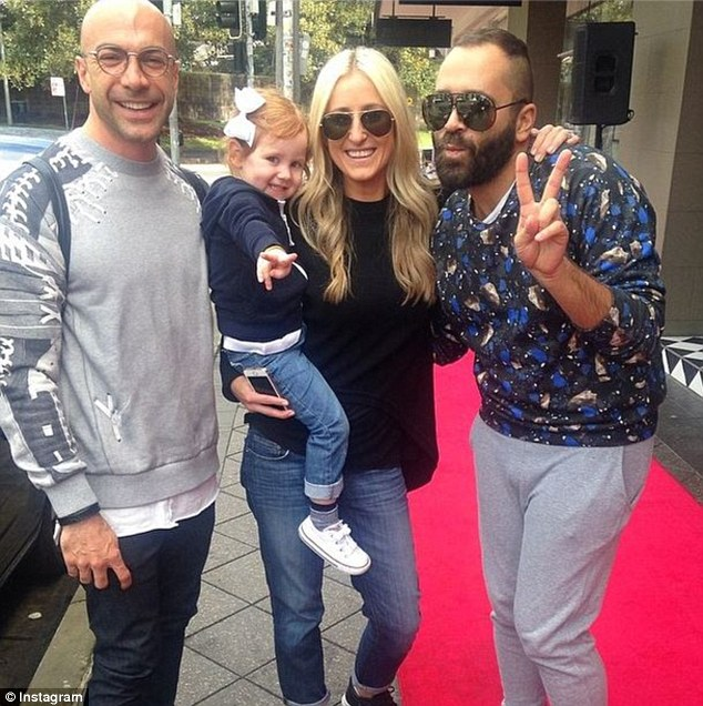 Peace: Roxy held her little girl as she playfully posed alongside friends Marco Lebel (L) and Chris Kontos (R)