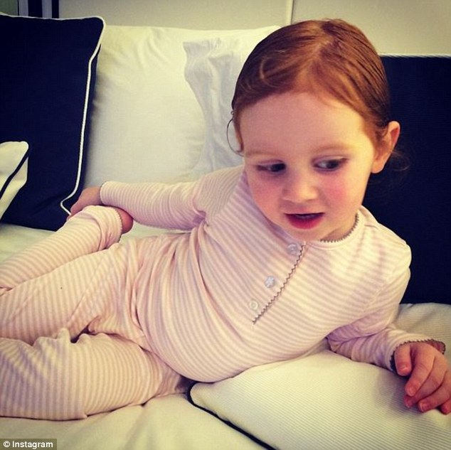 Pretty in pink: After a busy day the pint-sized red-head cuddled up to some pillows as she enjoyed a movie night