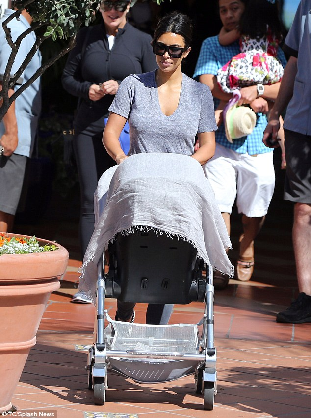 Stroller style: Kim Kardashian pushes baby North as she leaves her hotel to return home to Los Angeles