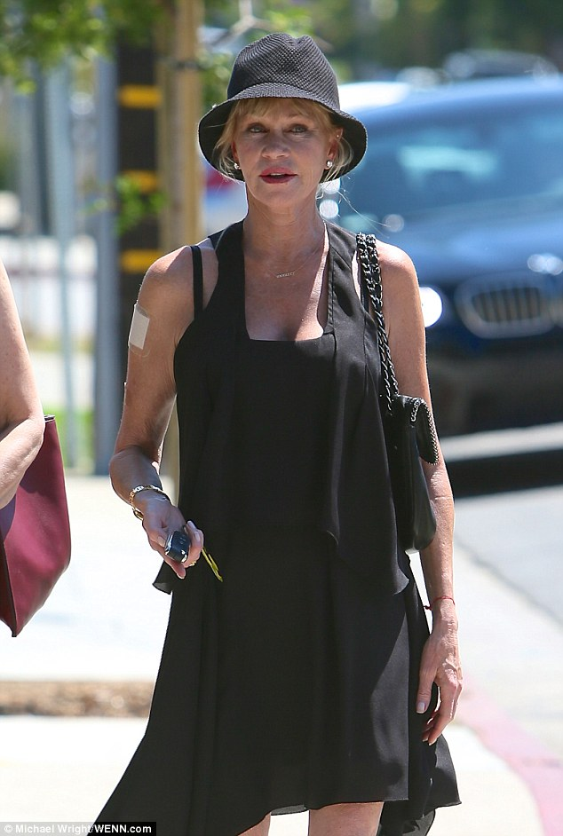 Stylish: Melanie kept it chic in a black sun dress with an asymmetrical hemline that showed off her long legs
