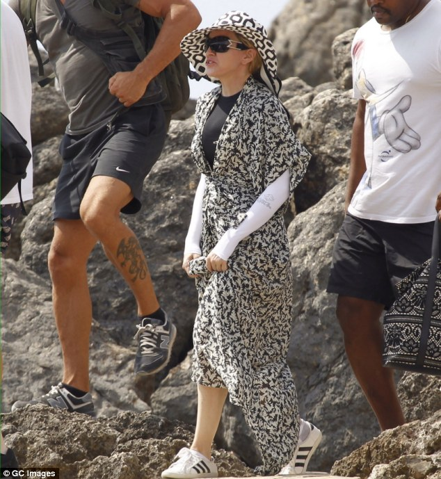 No rashing around: Madonna was pictured on a beach in Ibiza in a rashie, a long-sleeved Lycra top favoured by surfers, which she wore under her dress