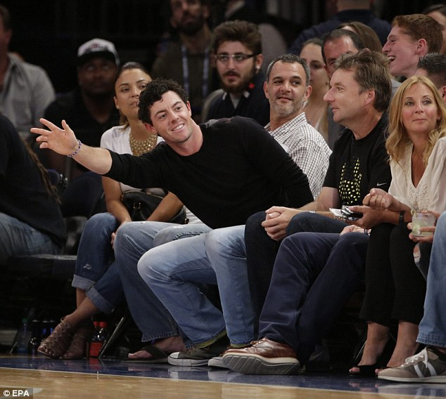 I'm over here: Golfer Rory McIlroy waves to Murray as he sits courtside in New York for USA v Puerto Rico