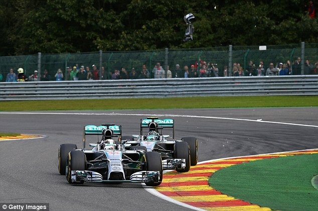 Debris flies: Part of Hamilton's car takes to the air after the clash during a controversial Belgian Grand Prix