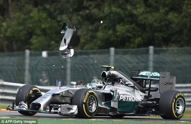Winging it: A piece of Hamilton's wing soars over German Rosberg's Mercedes after the high-speed collision