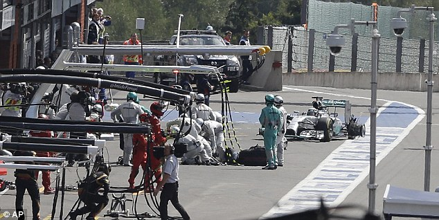 Ripped: Hamilton limps into the pits with a torn-up rear-left tyre after the incident on Sunday in Belgium