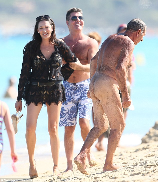 Steady on: Simon Cowell and Lauren Silverman can't control their mirth as a naturist trounces past during an outing on Pampelonne beach in Saint-Tropez